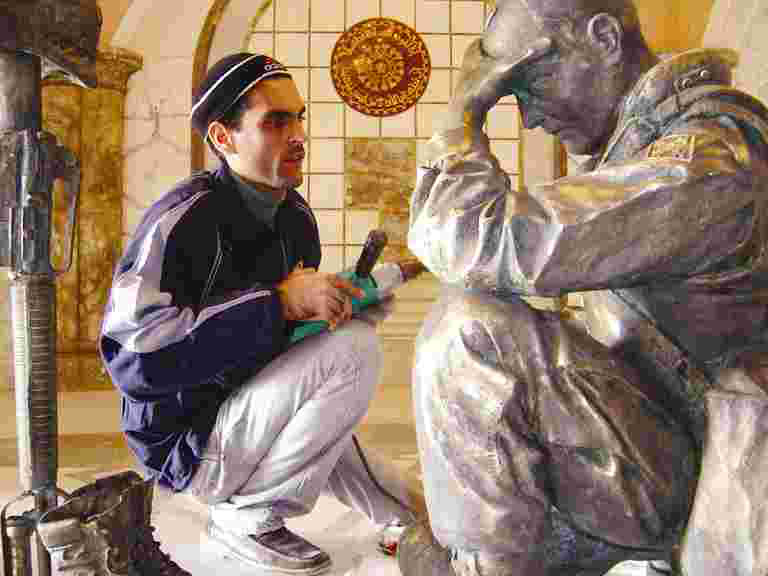 Iraqi sculptor Kalat examines the statue of an American Soldier made from melting down bronze statues of Saddam Hussein.